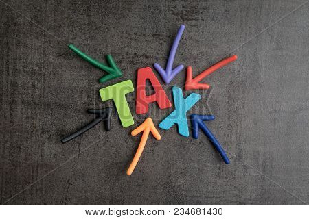 Tax Typography Text Concept, Magnet Arrows Pointing To The Word Tax At The Center On Black Cement Wa