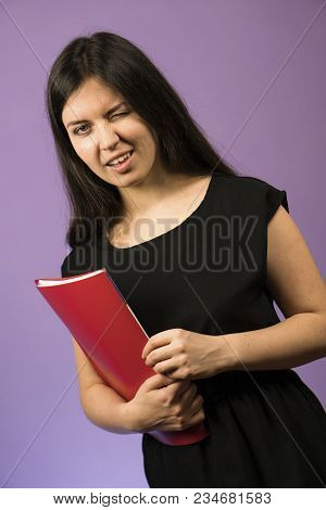 Young Woman In Black Dress With Red Notebook On Purple Background. Employee Girl Winking With Red Fo