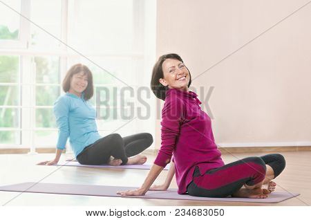 Active Sportive Women Doing Exercise In A Gym. Two Women Doing Stretching Exercises And Practicing Y