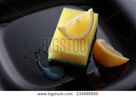 Black Plate And Dish Sponge . Lemon Slices . Conceptual Image On The Theme Of Purity And Freshness .