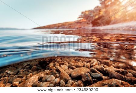 The stony bottom is seen through the clear waters of the Mediterranean sea, summer vacation on a luxury beaches of Greece
