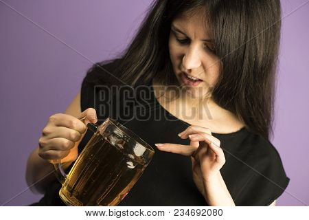 Cute Brunette Girl On A Purple Background Demonstrate Shis Dislike To Pint Of Beer