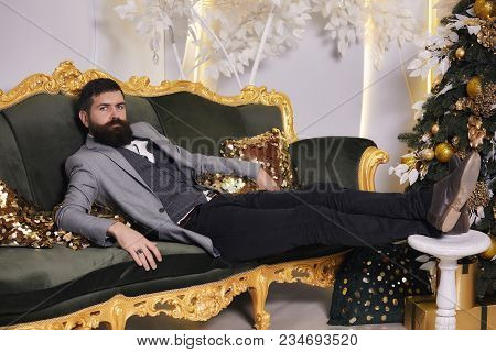 Christmas Day Concept. A Bearded Man In A Gray Classic Suit Is Relax Near A Christmas Tree. Handsome