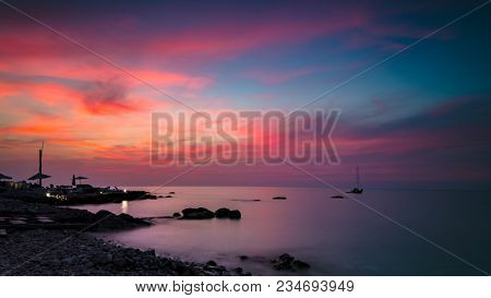 Beautiful pink sunset landscape, amazing view on the colorful dramatic sky over stony beach, peaceful place for summer vacation, romantic beach resort on the shore of Mediterranean sea, Lebanon