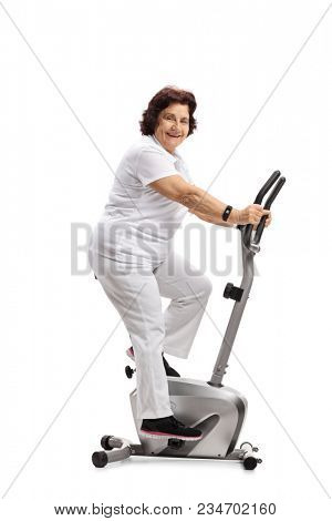 Elderly woman exercising on a stationary bike and looking at the camera isolated on white background poster