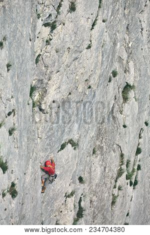 Old-aged Man Rock Climber Climbs On The Cliff. The Climber Climbs To The Top Of The Mountain.