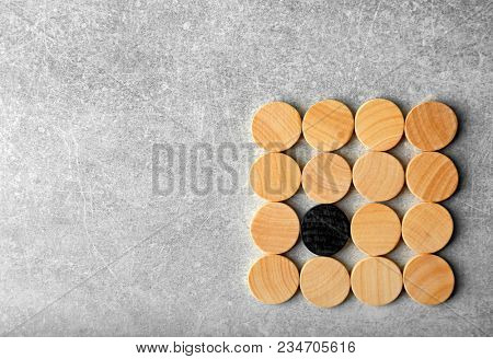 One black circle among wooden ones on light background. Difference and uniqueness concept