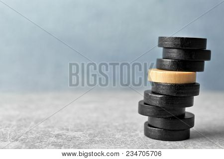 One wooden circle among black ones in stack on table. Difference and uniqueness concept