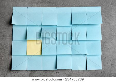 One yellow sticky note among blue ones on gray background. Difference and uniqueness concept