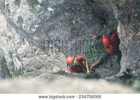 Man Rock Climber Climbs On The Cliff. The Climber Climbs To The Top Of The Mountain. Top View