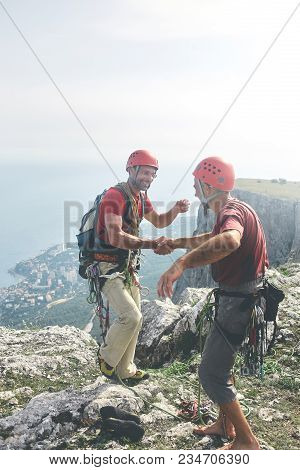 Two Man Rock Climbers Climbed On The Cliff. Happy Climbers On The Top Of The Mountain. Friends Hug A