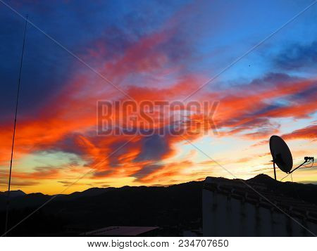 Silhouette At Orange Dawn Clouds In Andalusian Village