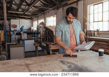 Skilled Young Artisan Standing At A Workbench In His Woodworking Studio Using A Digital Tablet And R