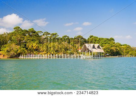 House Of Wood And Grass On Tropical Beach In Guatemala, Santo Tomas. Hut On Sea Shore On Sunny Blue