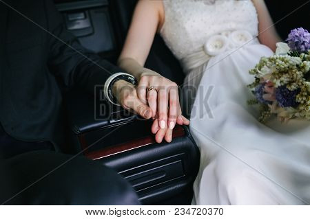 Elegant Couple Of Newlyweds Riding In The Back Seat Of A Luxury Car. Closeup Of Newlyweds Hands Held