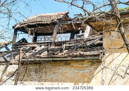 Damaged House. Damaged And Broken Collapsed Roof Of The Abandoned House After Fire From Grenade Bomb