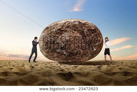 Businessman rolling a giant stone