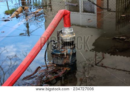 Partially Submerged Water Pump Pumping Water From Flooded Garden Through Large Red Hose With House A