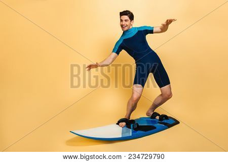 Full length portrait of a smiling young man dressed in swimsuit surfing on a board isolated over yellow background