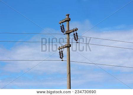 Concrete Electrical Power Line Utility Pole With Three Connected Wires On Blue Cloudy Sky Background