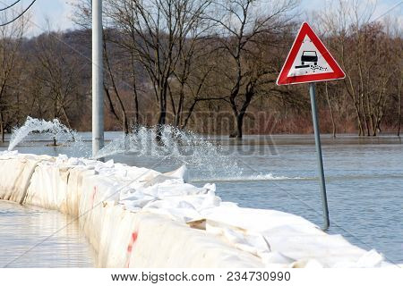 Flooded Soft Verge Road Sign Next To Box Barriers Flood Protection With Pumps Pumping Water, Trees,
