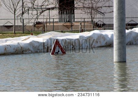 Flooded Work Or Construction Ahead Road Sign In Front Of Box Barriers Flood Protection And Next To C