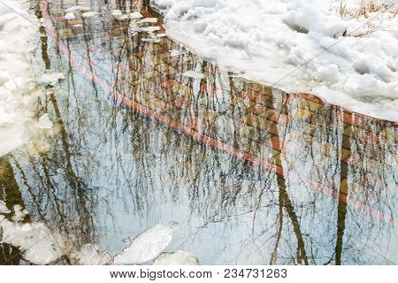 Flooding Of Tile Walkpath Due To Snow Melting And Rising Of Water Level. Blue Sky In Puddle Reflecti