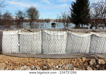 New Sandbox Barriers Flood Protection Partially Covered With Geotextile Fabric, Massive Rocks In Fro