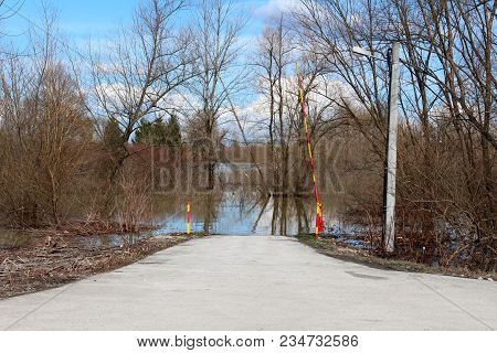 Open Red And Yellow Metal Ramp Leading To Flooded Forest Road Next To Utility Post With Trees Withou