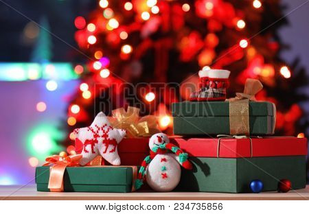 Wrapped gifts on table against blurred festive lights. Boxing day