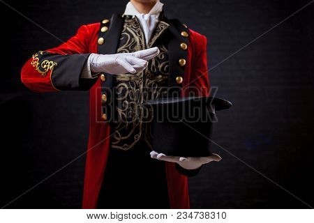 Magician Illusionist, Close-up Of Hand In Gloves The Guy In The Red Camisole And The Cylinder. Holds