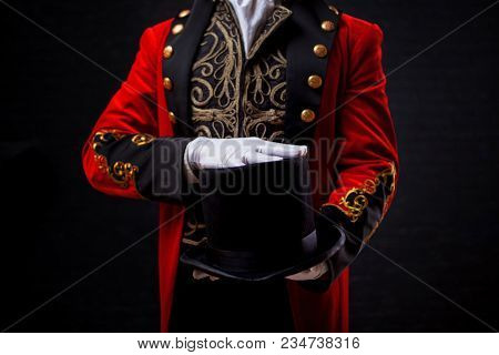 Magician. Close-up Of Hand In Gloves The Guy In The Red Camisole And The Cylinder. Bright Tailcoat,