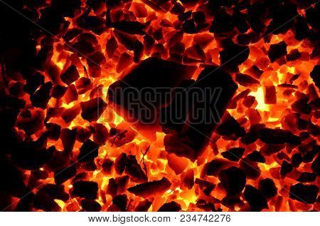 A Decomposed Large Piece Of Coal On A Burning Shallow As A Background.