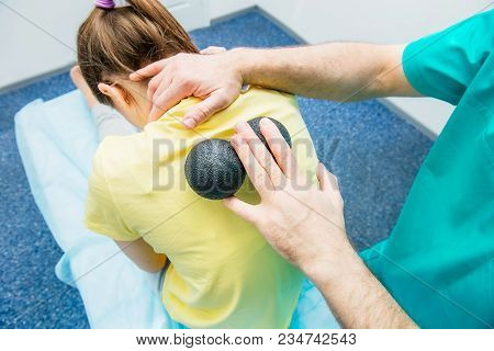 Woman At The Physiotherapy Receiving Ball Massage From Therapist. A Chiropractor Treats Patient's Th