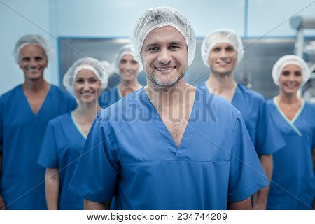 Team Of Surgeons. Smart Experienced Male Surgeon Standing In Front Of His Team And Looking At You Wh