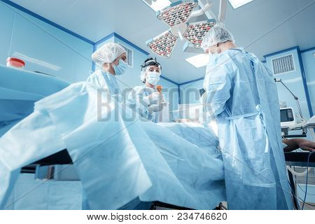 Professional Surgical Team. Team Of Professional Nice Skilled Doctors Standing Around The Patient An