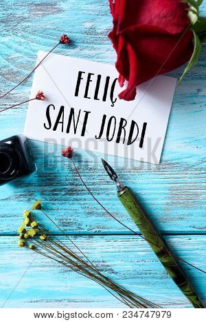 high angle view of a red rose, an ink bottle, a nib pen and the text Felic Sant Jordi, happy Saint George Day in Catalan, when it is tradition to give red roses and books in Catalonia, Spain