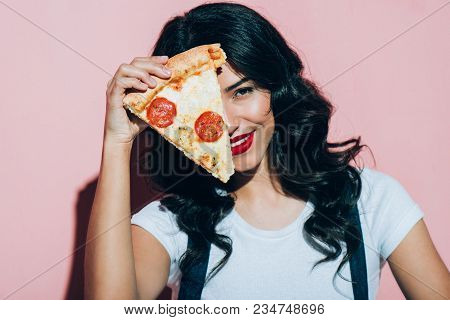 Obscured View Of Beautiful Smiling Woman Covering Eye With Piece Of Pizza On Pink Background