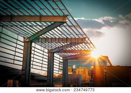An artistic metal architectural structure attached to a downtown glass building during a sunset with dramatic sun rays.