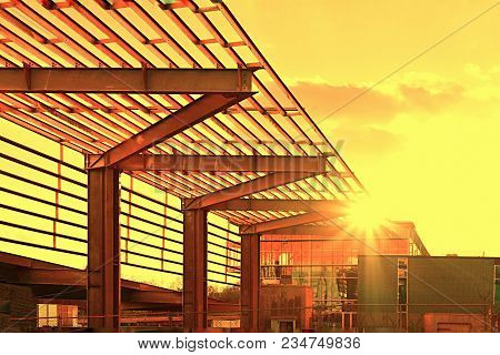 An architectural metal art structure connected to a modern downtown building in a golden yelliw sunset.