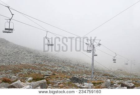 Mountain Cableway Chairlift In Clouds And Fog, High Angle Side View