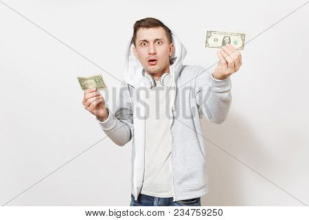 Young Handsome Shocked Man Student In T-shirt And Light Sweatshirt With Hood With Headphones Holds O