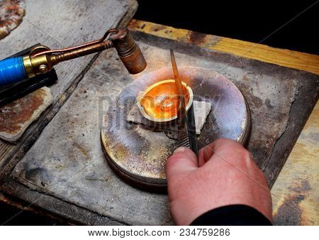 Close-up Of The Work Of A Jeweler. Melting Gold In A Bowl With A Burner.