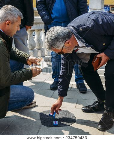 Venice, Italy - March 28, 2018: Con Artists Performing Shell Game Scam To Suspecting Victims Using M