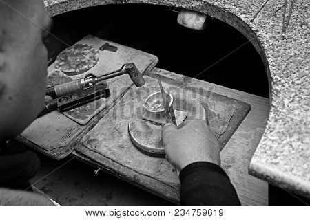 Black And White Photo Of A Jeweler In The Workplace. The Jeweler Melted The Gold In The Bowl.