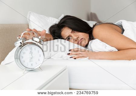 Image of dissatisfied woman 20s lying in bed on pillow and turning off ringing alarm clock on nightstand