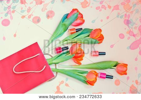 Fresh Orange Tulip Flowers And Nail Polishes In Paper Bag On Beige Background. Top View With Copy Sp