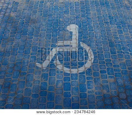 Top View On Parking Sign For Disable People. Disabled Parking Space And Wheelchair Symbols On Paveme