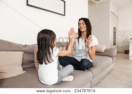 Picture of happy people woman and little child playing together patty cake resting on sofa in living room