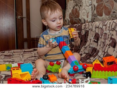 Sweet Little Boy Building Tower From Cubes At Home.